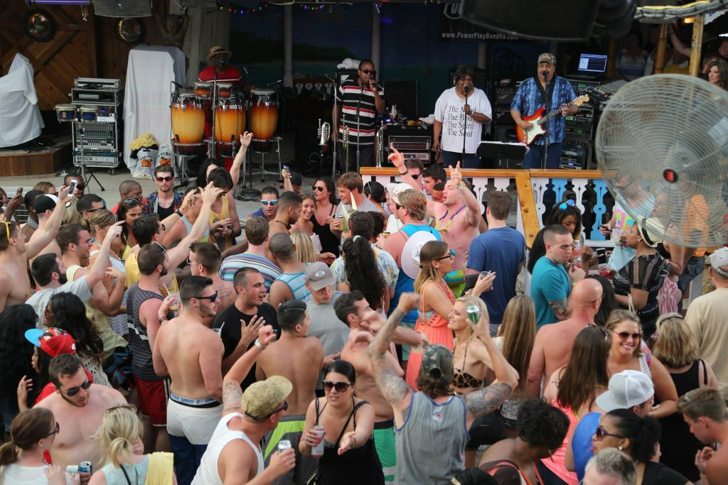people party to a live band on a beach