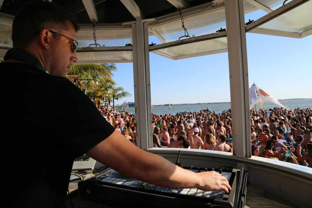 a DJ plays a live set from a booth on a beach