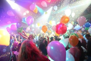 balloons and confetti fall from the ceiling at a night club