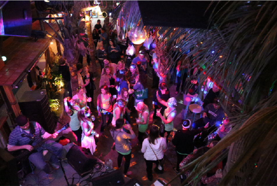 people listen to live music at a tiki bar