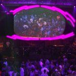 a large screen shaped like an eye shows a crowd