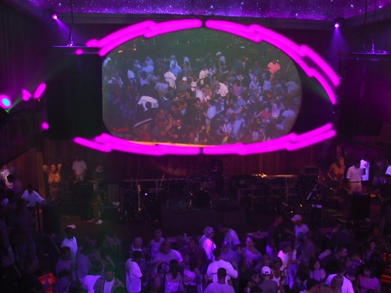 a large screen shaped like an eye shows a crowd