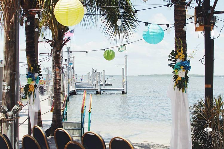 a wedding is set up on the beach with the bay in the background