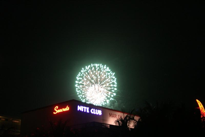 a firework explodes above a nite club billboard