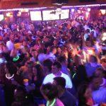 people wear glowsticks and dance in a nightclub