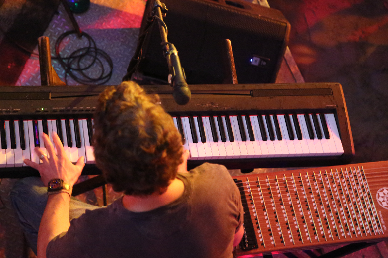 a keyboardist plays surrounded by sound equipment