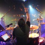 drummer raises a stick at a concert
