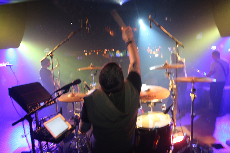 drummer raises a stick at a concert