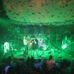 a band with green lights plays as confetti falls