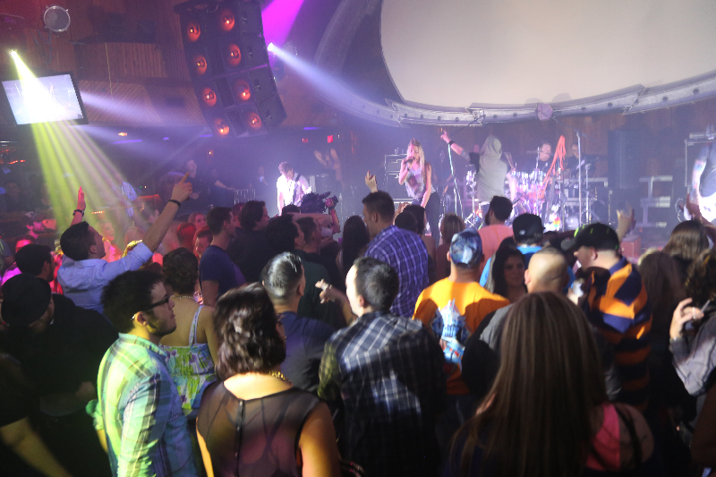 a crowd watches a band play live on stage