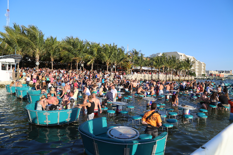 a group of people lounge in teal seats in the water
