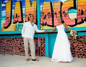 a bride and groom smile in front of a Jamaica USA sign