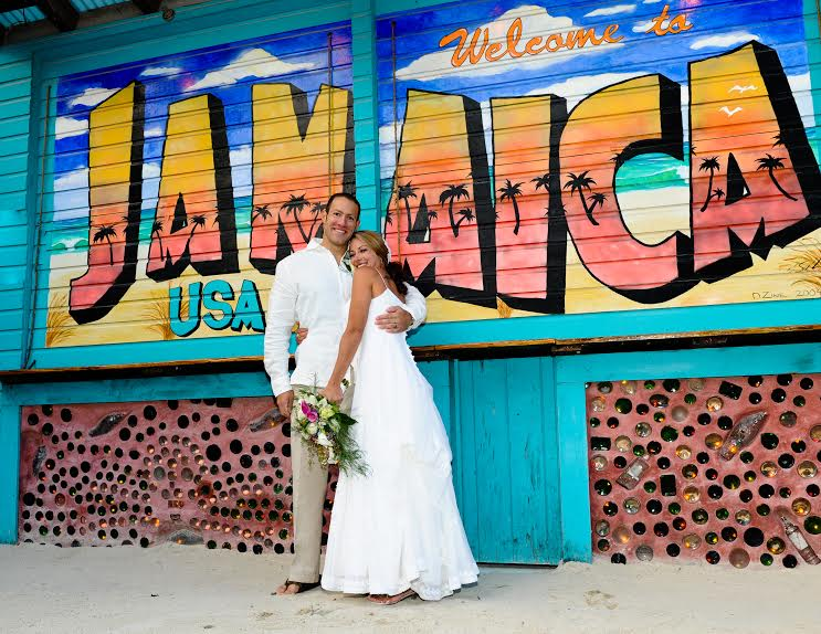 a bride and groom pose in front of a large sign