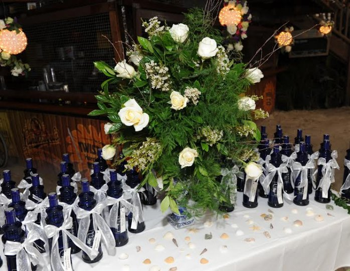 a table full of bottles with white bows