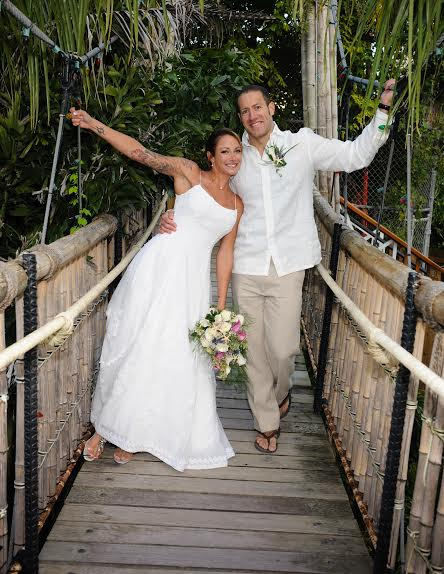 a bride and groom pose on a bamboo bridge