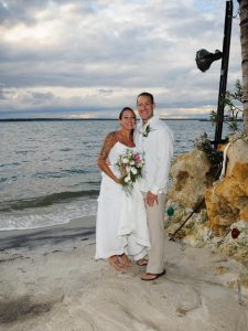 a bride and groom pose on a sandy beach
