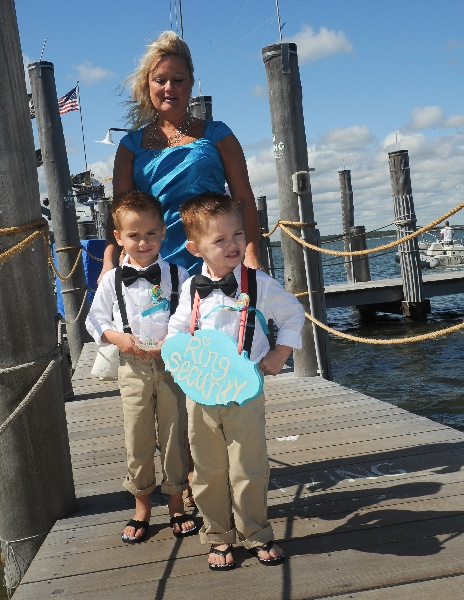two young boys are escorted down the dock for a wedding