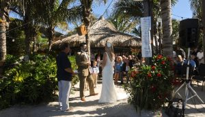 a wedding ceremony on beach under palm trees
