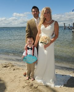 a bride and groom pose with boy on beach
