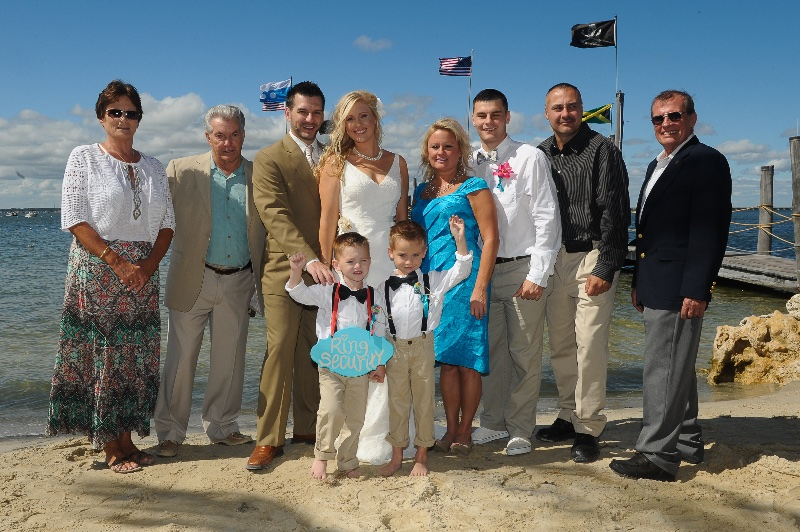 a wedding party pose on a sandy beach