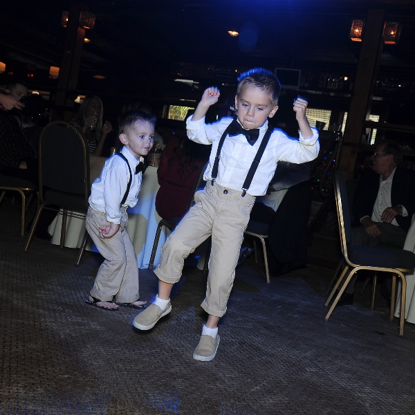 two young boys dance at a wedding