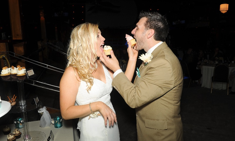 bride and groom feed each other cupcakes at wedding
