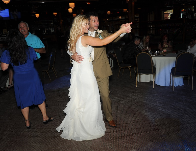 a bride and groom dance and point