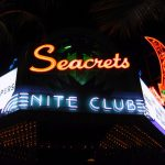 a neon sign for seacrets nite club entrance