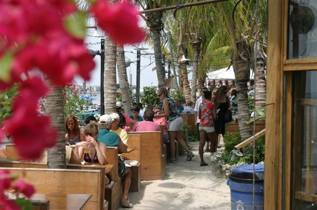 people sit at a line of booths in the sand