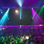 nightclub lights project colors onto a crowd of people