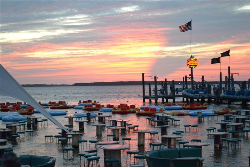 a sunset over water with dock and dining area