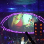 a large screen shows dancers at a nightclub