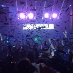 stage lights shine on a crowd with falling confetti