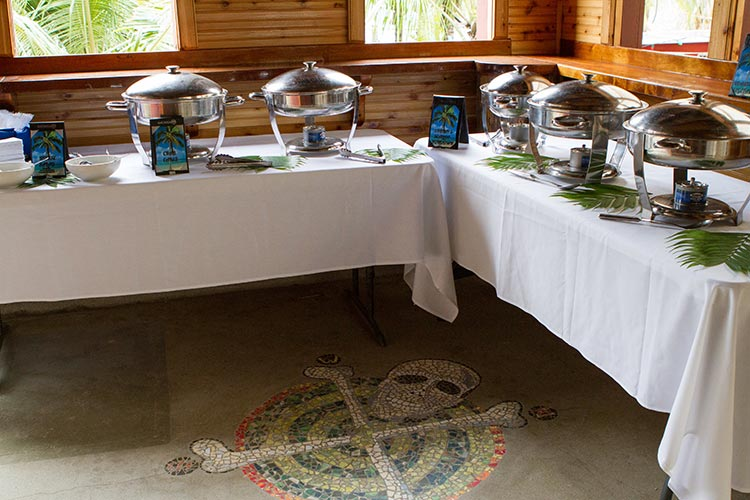 two buffet tables with circular hot trays and skull on the floor