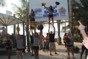 cheerleaders perform on sand