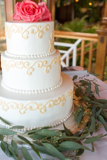 a white wedding cake with leaves around the base