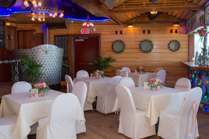 a room with white table cloths and chair coverings for a wedding