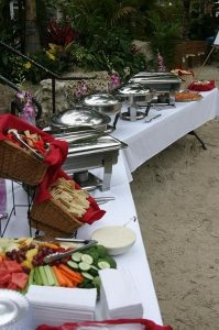 a table at a buffet laid out on the beach